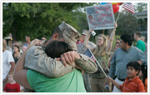 Soldier Returns Home and hugs a family member
